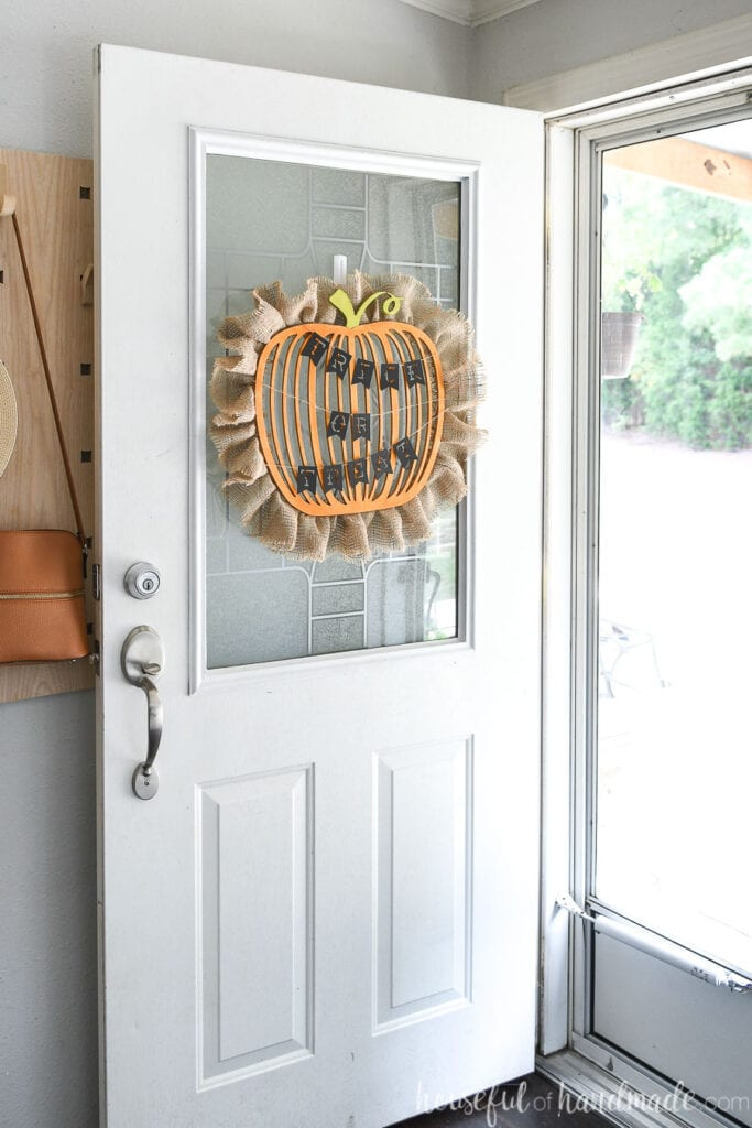 Entryway with door open showing the pumpkin wreath hanging on it with the Trick or Treat banner.