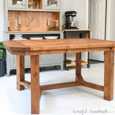 DIY trestle dining table with 2 leaves in the dining room in front of a hutch.