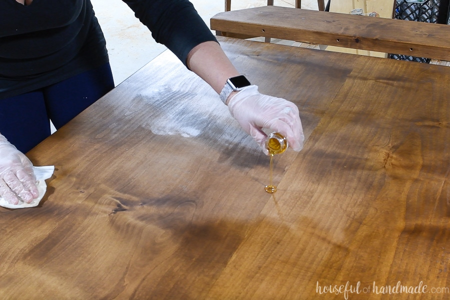 Pouring a puddle of TrueTone buff in finish on the stained table top.