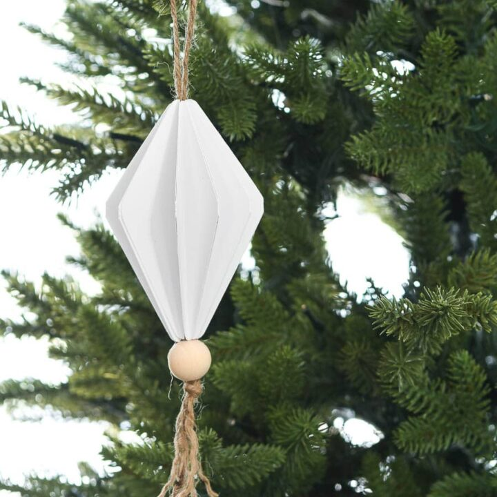Diamond shaped paper Christmas ornament hanging on a Christmas tree.