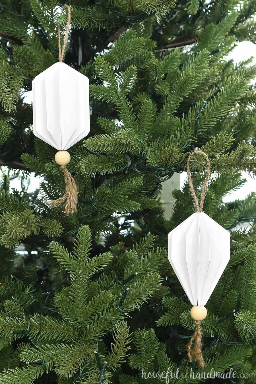 Two jewel shaped Christmas ornaments made from paper hanging on a Christmas tree.