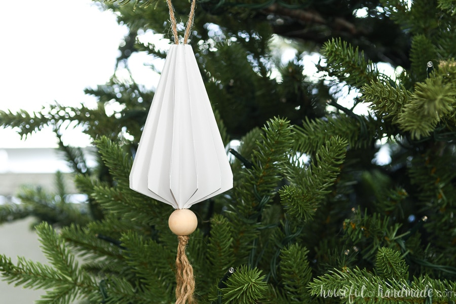 Christmas tree without lights and a white paper tree triangle shaped jewel shaped Christmas ornament hanging on it.