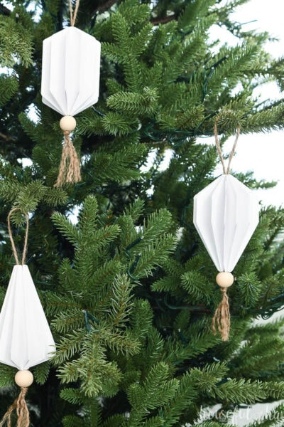 Three white jewel shaped paper Christmas ornaments with tassels and wood beads on the bottom hanging on an unlit Christmas tree.