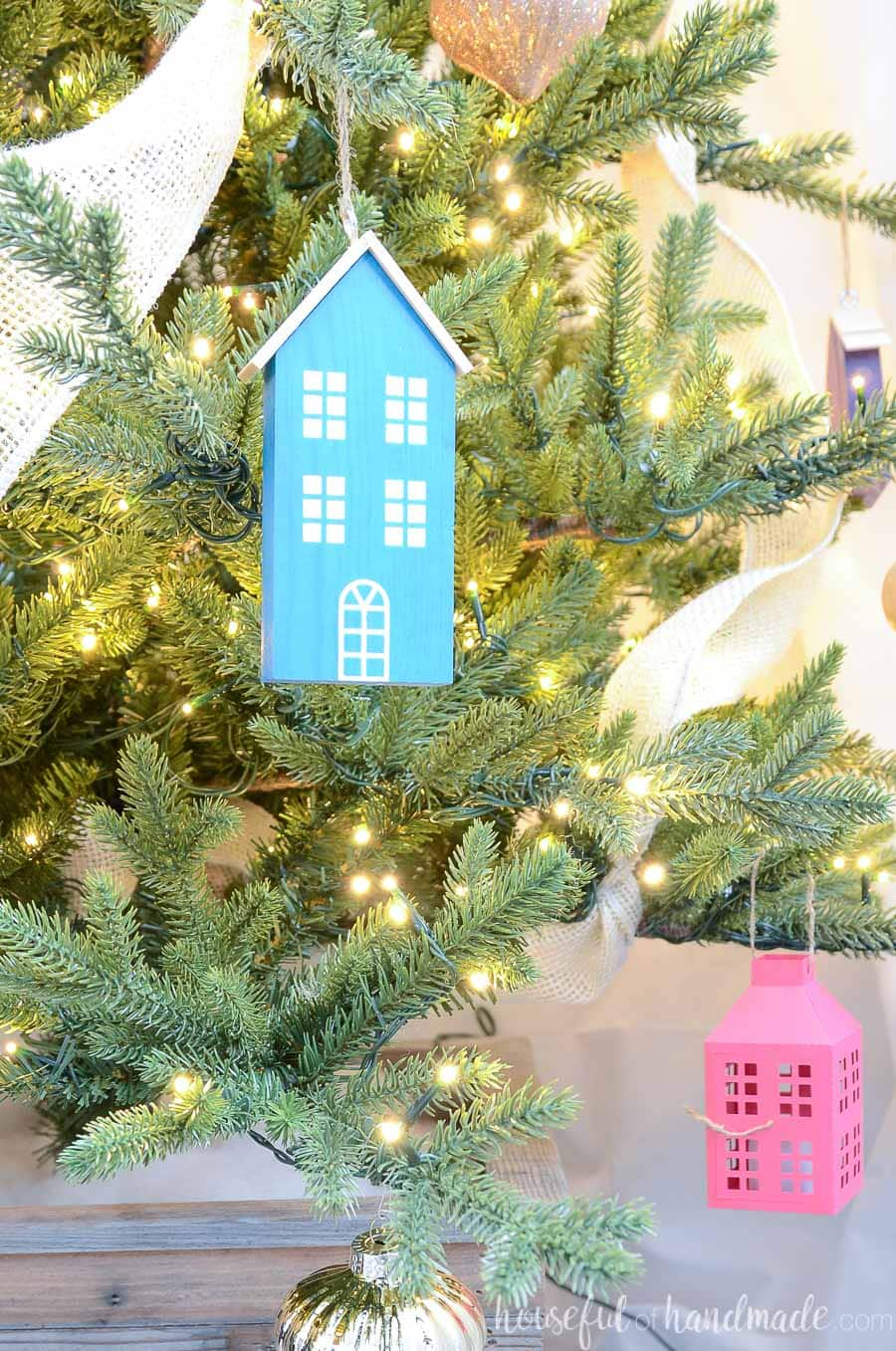 Close up of the tall blue scrap wood Christmas house hanging on a Christmas tree.
