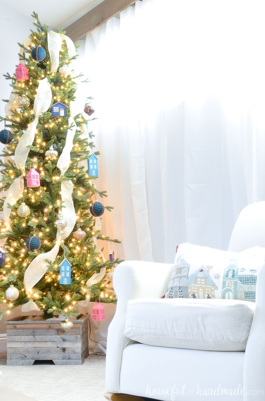 Chair in the foreground and Christmas tree in the background decorated with color full ornaments include the wood Christmas houses made from scrap wood.