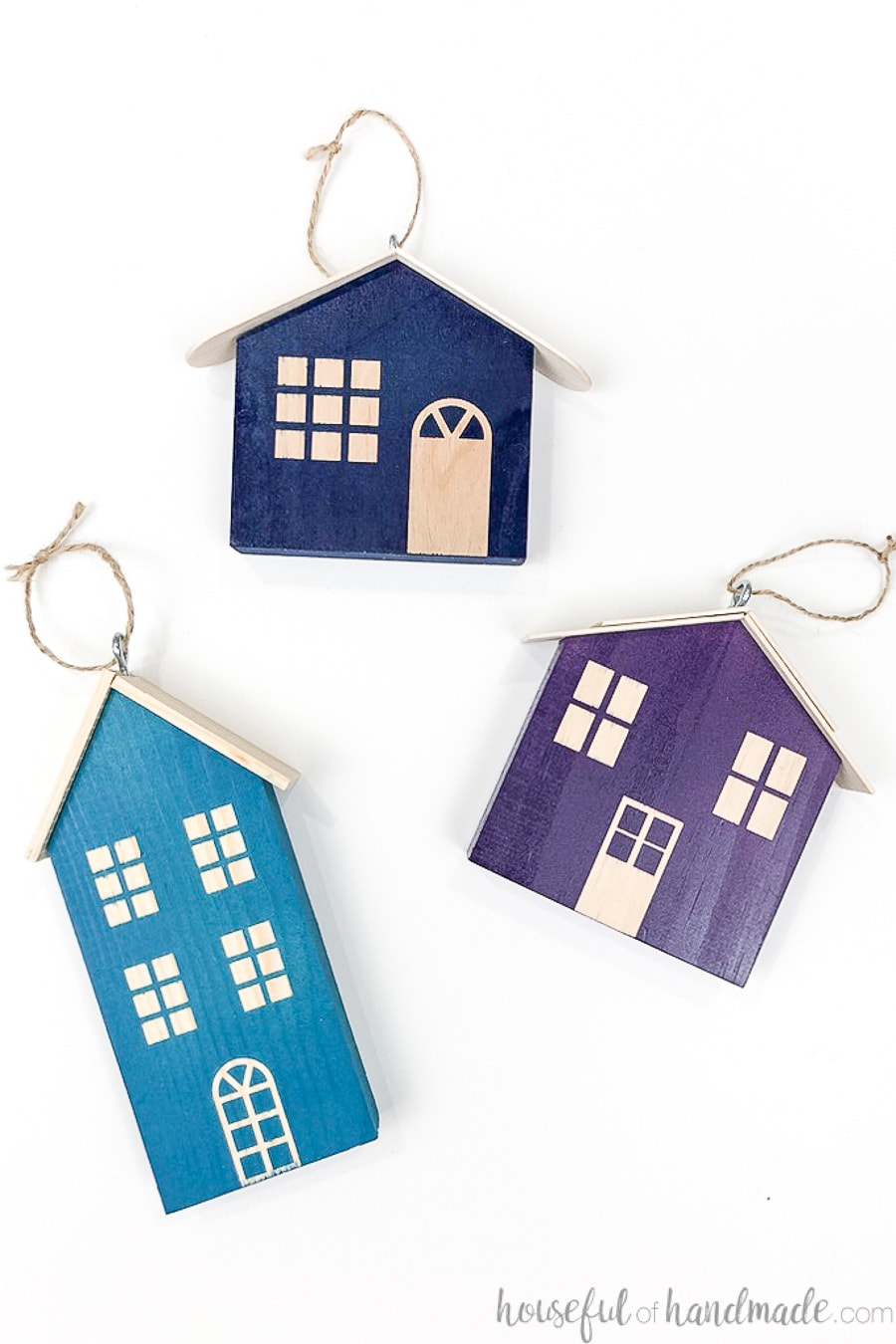 Three wood Christmas houses with eye hooks on the top to hang as ornaments, one turquoise, one navy and one purple, laying on a white background.