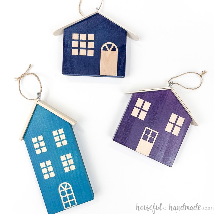 Square photo of 3 colorful wood Christmas house ornaments laying on a flat white surface.