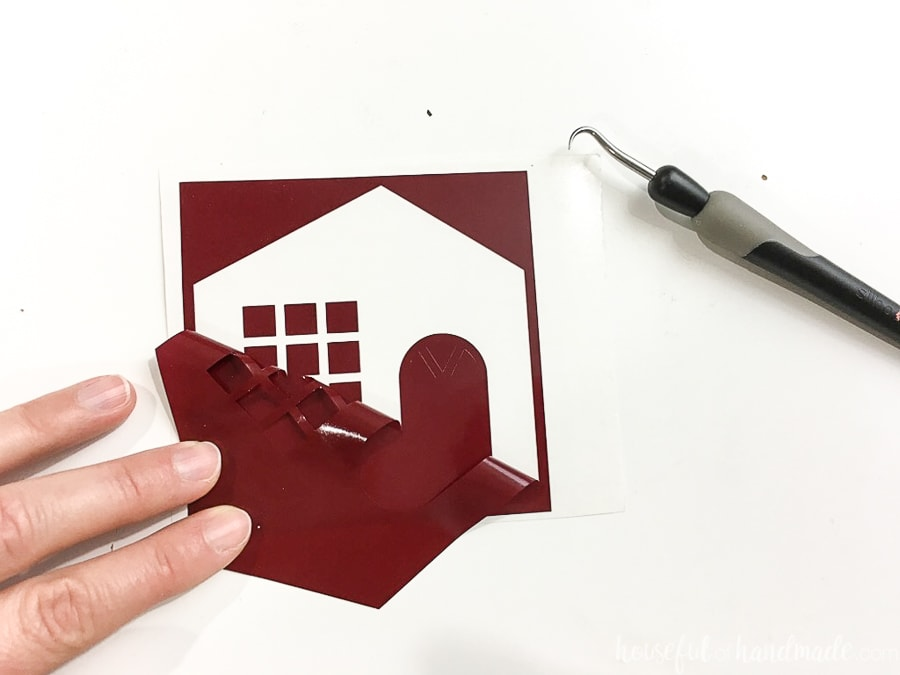 Dark red vinyl cut out with house template being weeded of the pieces you don't want.