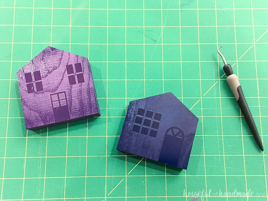 Two of the houses painted with navy and purple paint with the vinyl still on it.