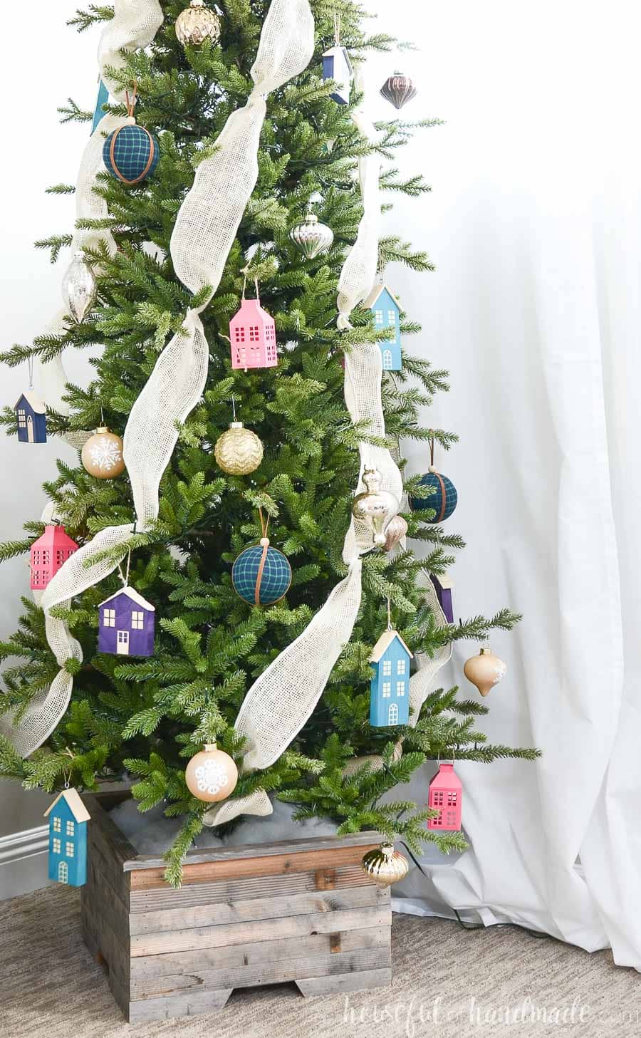 Showing some of the wood Christmas house ornaments made from scrap wood hanging on a Christmas tree decorated with jewel tones in a reclaimed wood Christmas tree stand.
