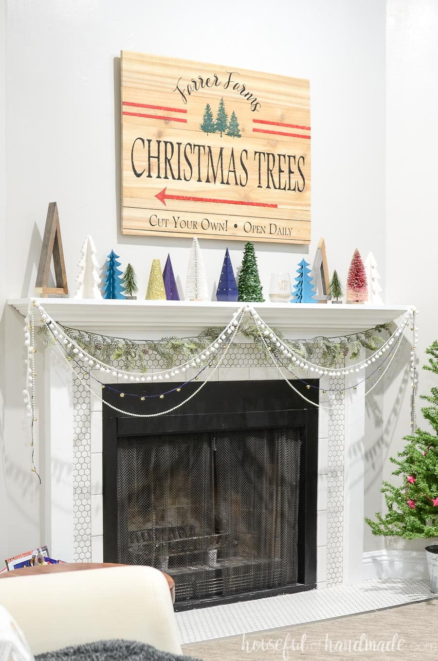 Christmas mantel decorated with reclaimed wood Christmas trees, porcelain Christmas trees and paper Christmas trees with a Christmas tree farm sign above it.