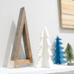 Simple decorative Christmas tree made from reclaimed wood on a mantle next to other decorative Christmas trees.