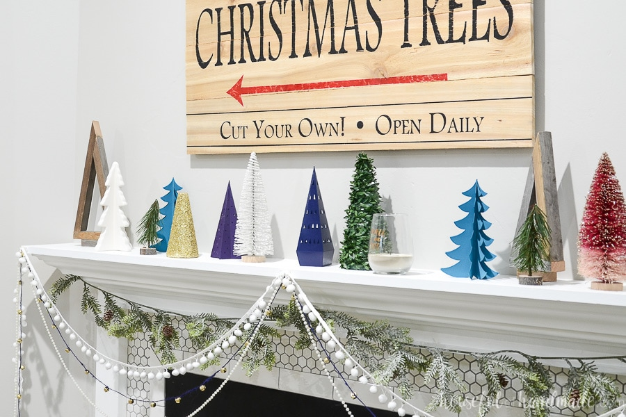 White mantel with lots of Christmas trees on it, including the wood Christmas trees made from 1x2 boards.