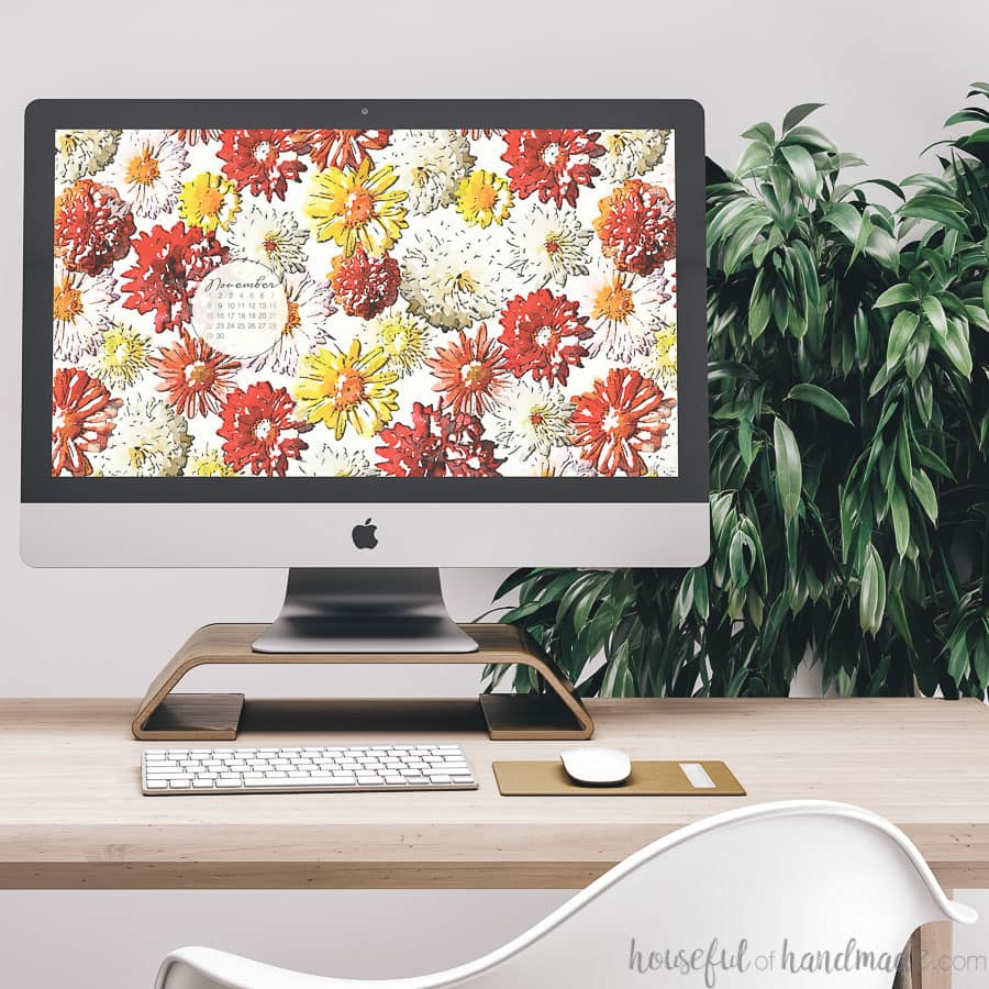 Desktop computer showing the free digital background for November on the screen sitting on a desk in front of a plant.