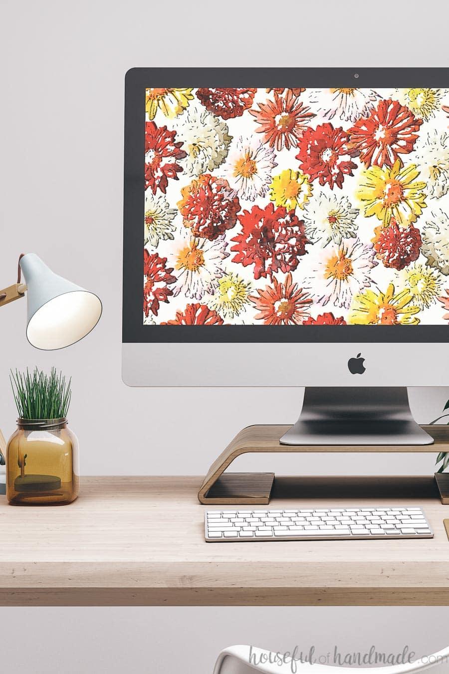 iMac desktop computer with watercolor fall mum print on the screen as digital wallpaper.