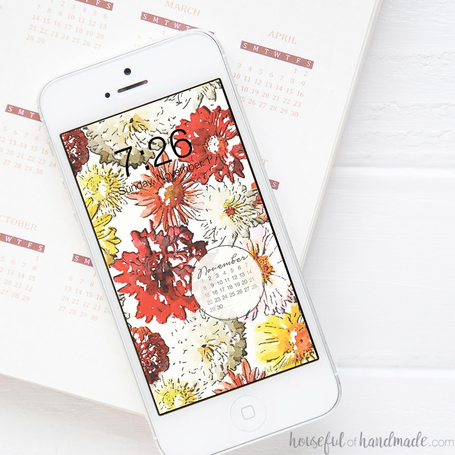 White iphone sitting on a planner with the free digital wallpaper for November showing on the home screen.
