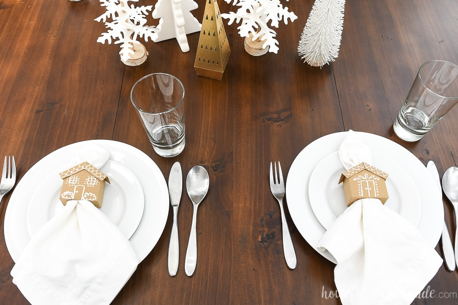 Two place settings on the side of the table with the gingerbread house napkin rings sitting on the place settings.