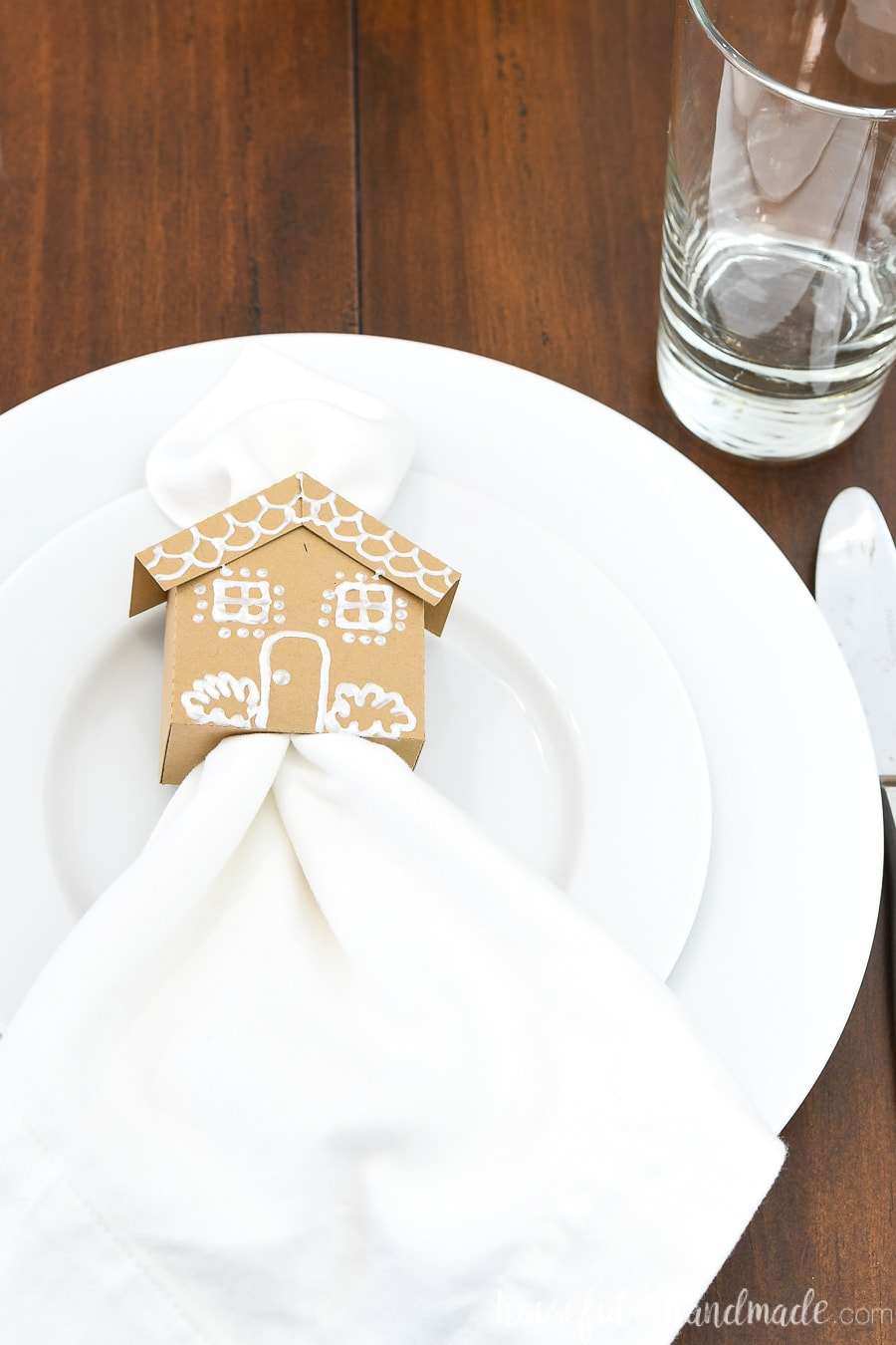 Close up of the paper gingerbread house napkin ring with a white fabric napkin inside sitting on a place setting.