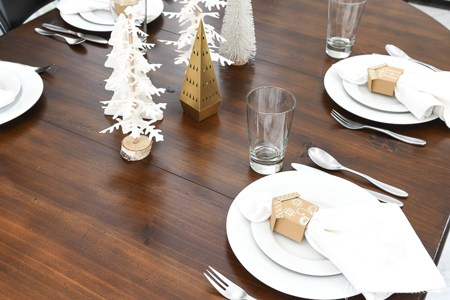 Looking on top of a table set for Christmas with Christmas trees and gingerbread house napkin rings.