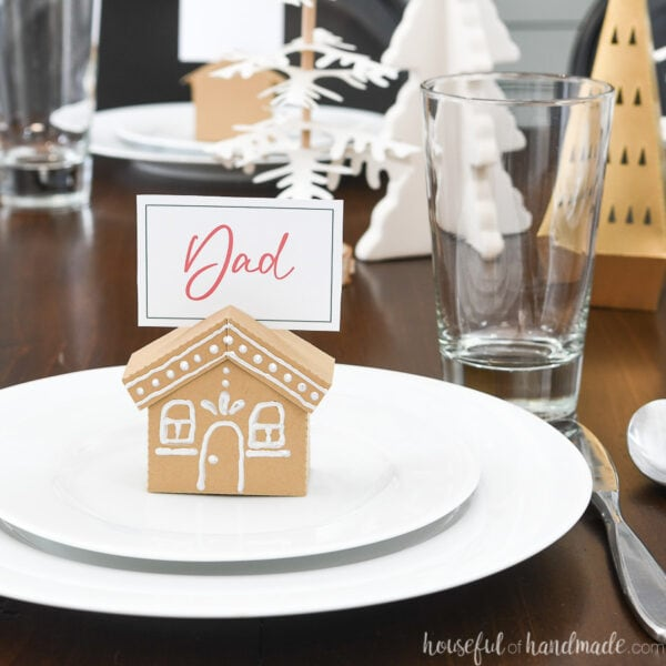 Place setting with a paper gingerbread house place card sitting on top of the salad plate.