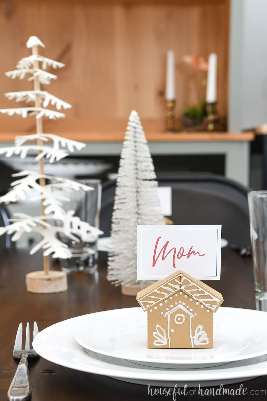 Christmas table set with Christmas trees as the centerpiece, white plates, with a brown paper gingerbread house place card holder sitting on them.