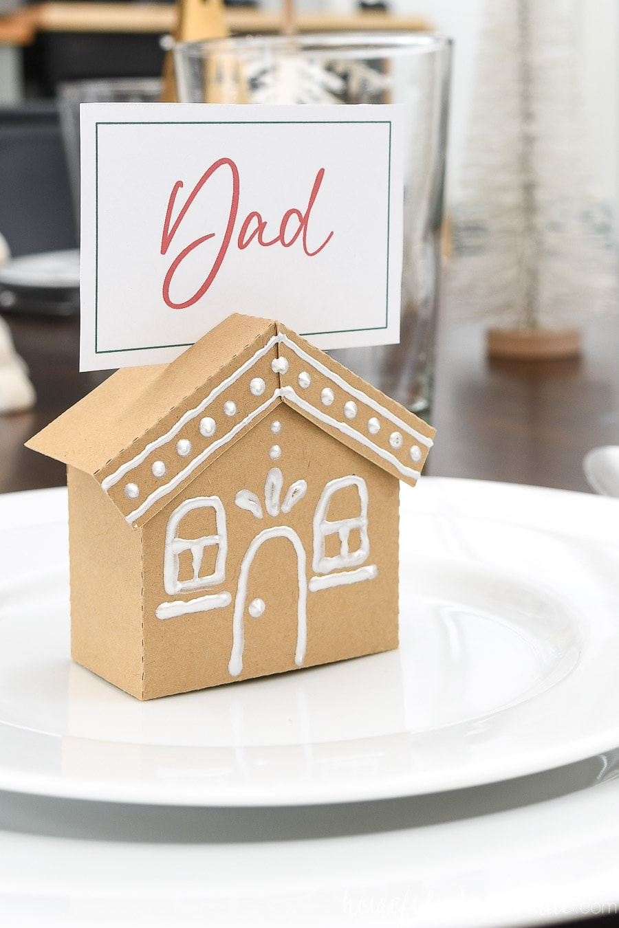 "Close up of the gingerbread house place card holder with a place card for ""Dad"" in the top."