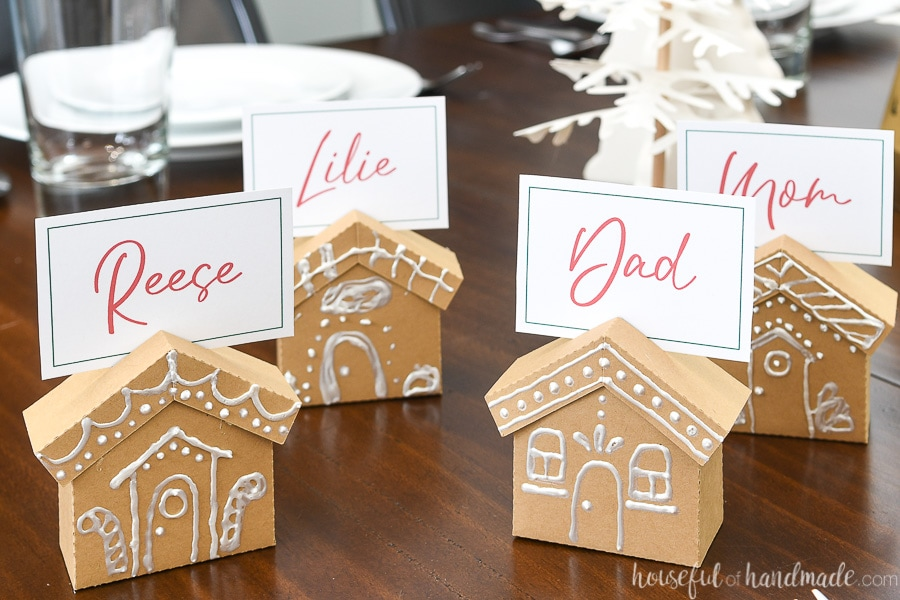 Four gingerbread place card holders made from paper on a table with family names on the place cards.