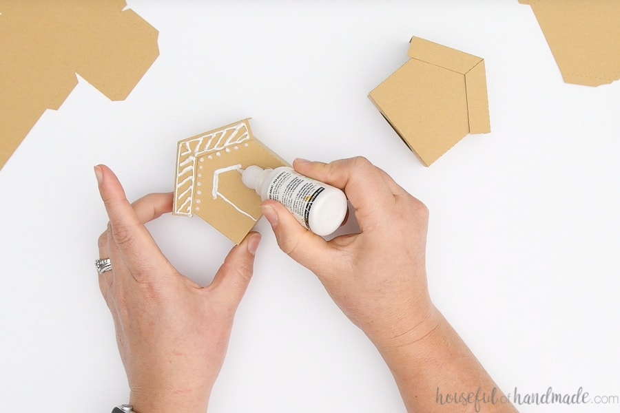 Decorating the front of the paper gingerbread houses with white puffy paint.