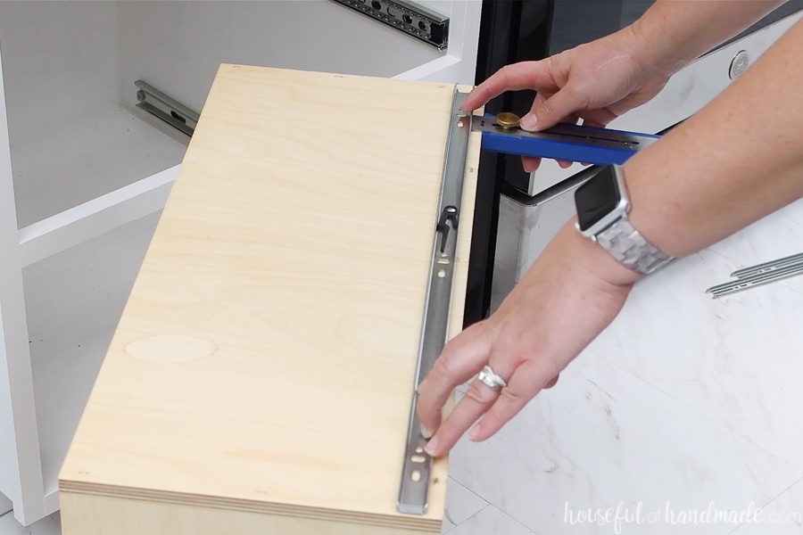 Using a Kreg multi-mark tool to measure the distance from the bottom of the drawer box to the inside of the drawer slide.