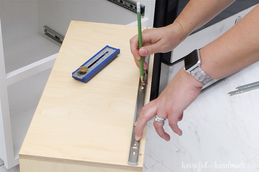 Marking where to drill pilot holes for the drawer slide piece attached to the drawer box with a pencil.