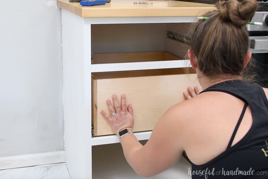 Pushing the drawer box fully closed to fully engage the ball bearing drawer slides for the first time.