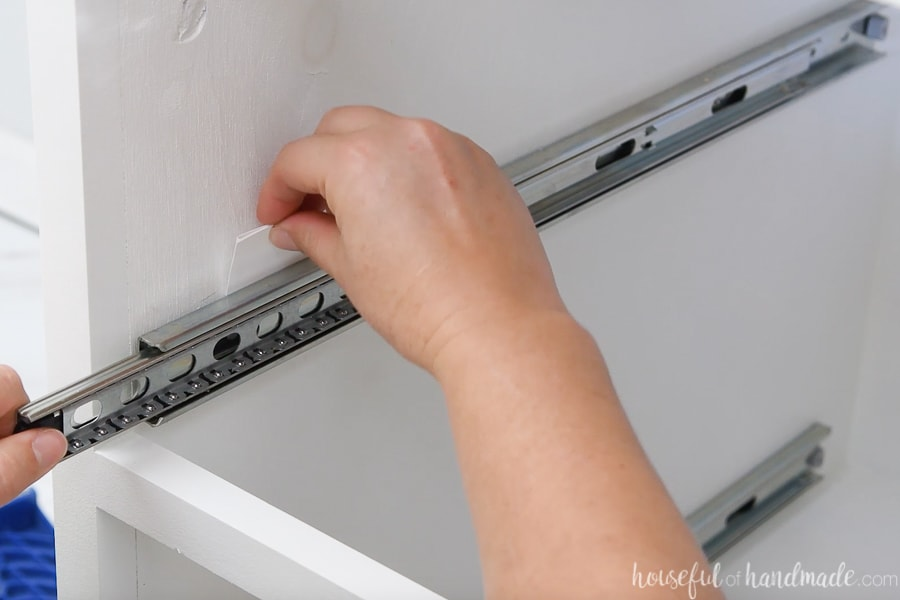 Shimming out the drawer slide on one side of the kitchen cabinet with a folded piece of coverstock paper.