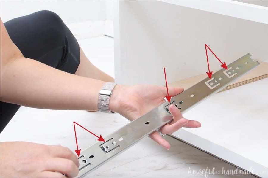 Photos with red arrows pointing to  the back side of the ball bearing drawer slide where there are 5 tab sections with screw holes in them