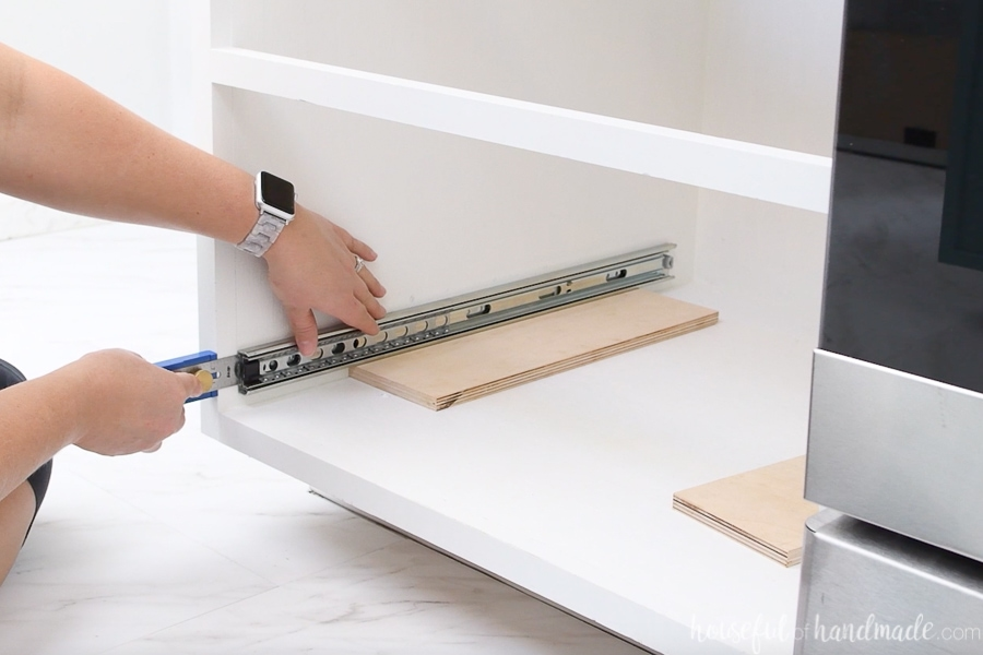 """The outside part of the ball bearing drawer slide sitting on a 1/2"""" piece of plywood inside the drawer base cabinet. Being measured from the front with a multi-mark tool."""