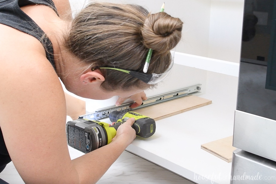 """Drawer slide sitting on a piece of 1/2"""" plywood on the bottom of and empty cabinet carcass and drilling a pilot hole in the front screw hole."""