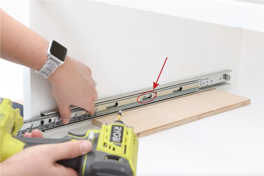Red arrow showing where the holes in the drawer slides are so you can move them around to access the screw holes.