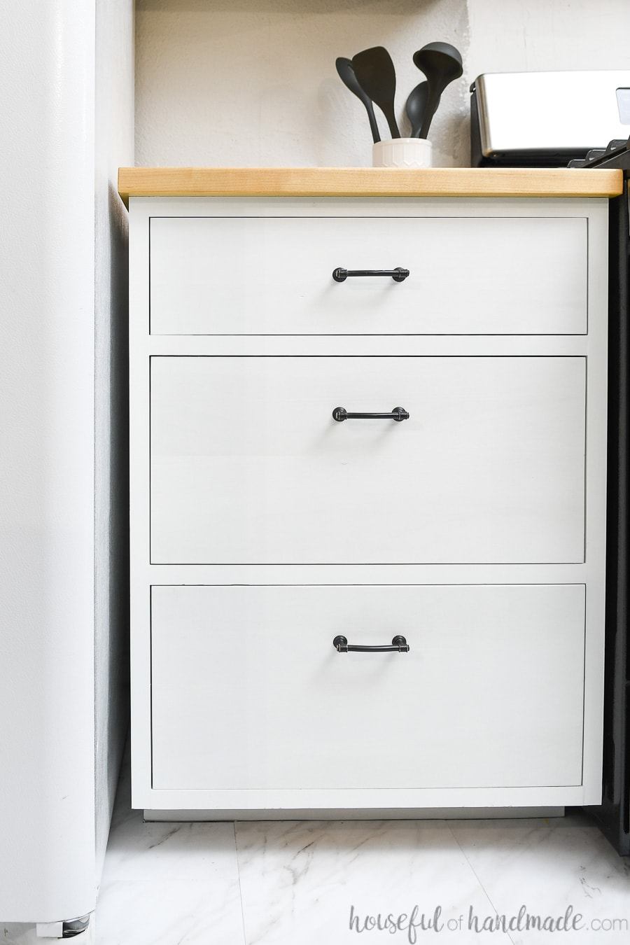 White 3 drawer base cabinet with rubbed bronze bar pulls and maple wood countertop on top.