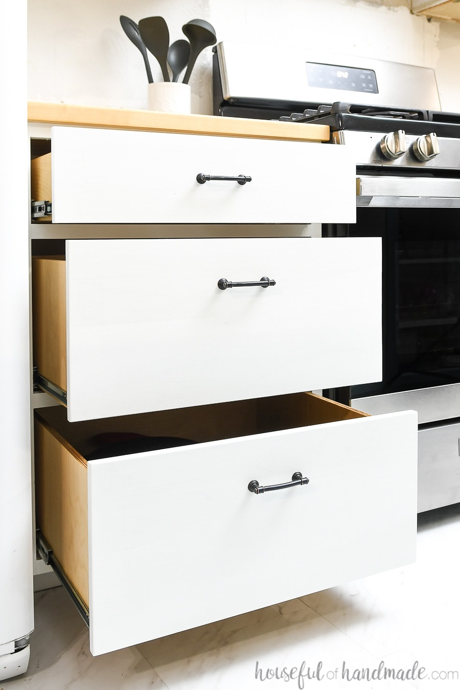 Three white kitchen cabinet drawers with black pulls pulled out partially showing the ball bearing drawer slides on the sides of the drawers.