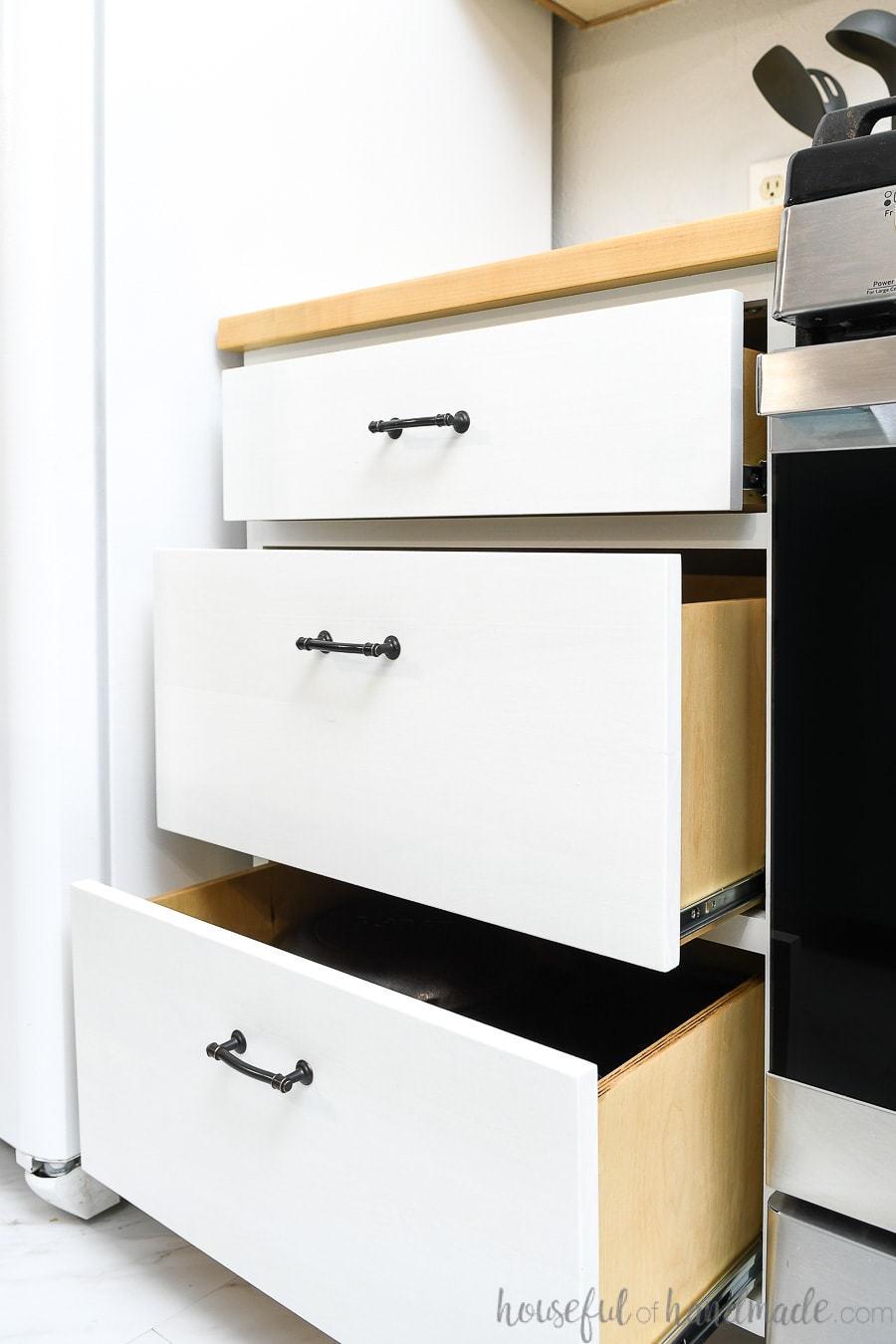 Three drawer cabinet next to a stove with the drawers pulled out in steps.