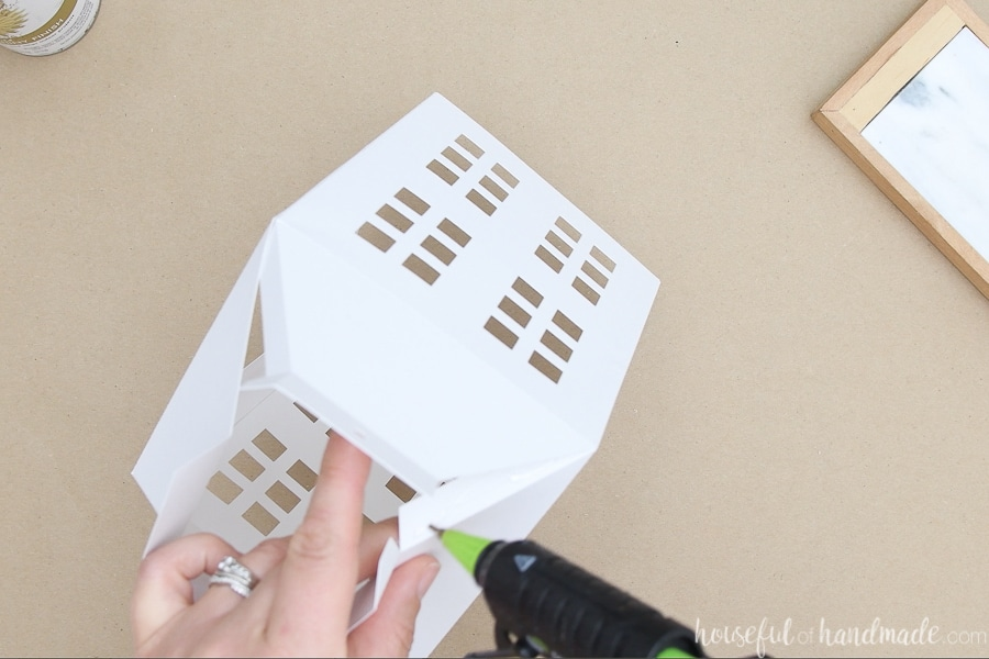Glueing the top flaps to create the tapered top of the paper lantern.