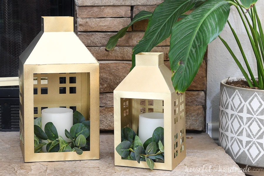 Gold paper lanterns decorated for Christmas on a stone hearth next to a houseplant.