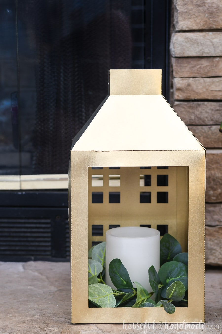 Close up of the inside of the large gold lantern filled with a ring of eucalyptus leaves and white faux candle.