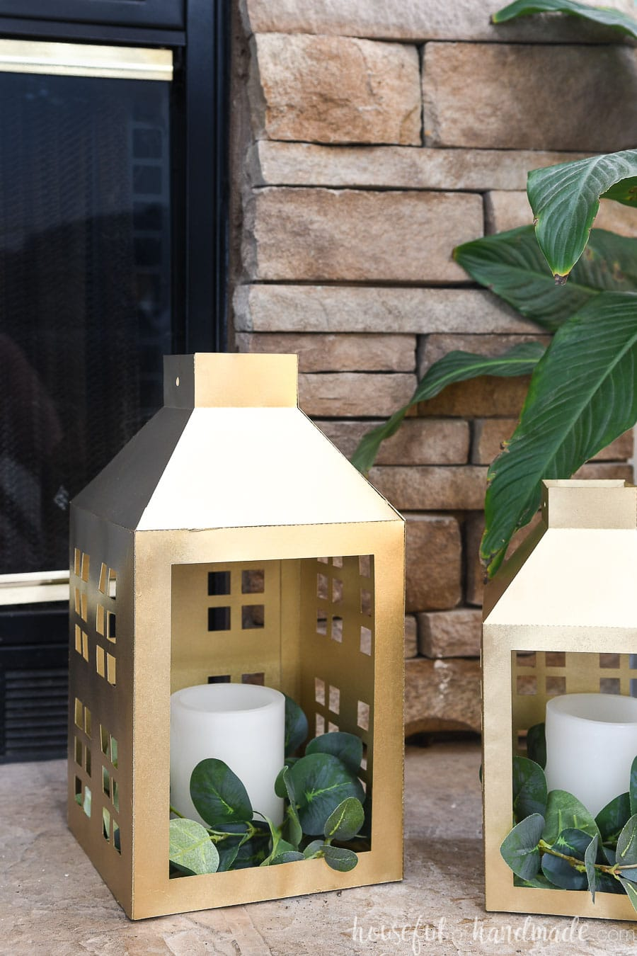 Two shiny gold painted paper lanterns with open fronts sitting in front of a stone fireplace decorated for Christmas.