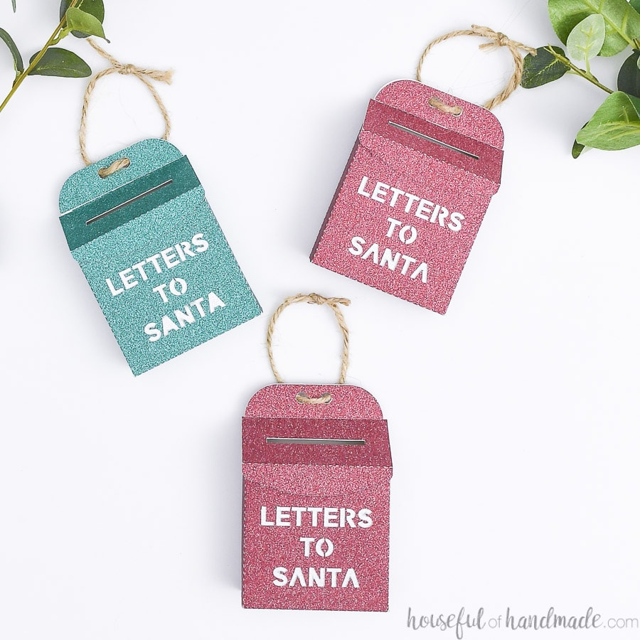 Red and green glitter santa mailbox ornaments on a white background.