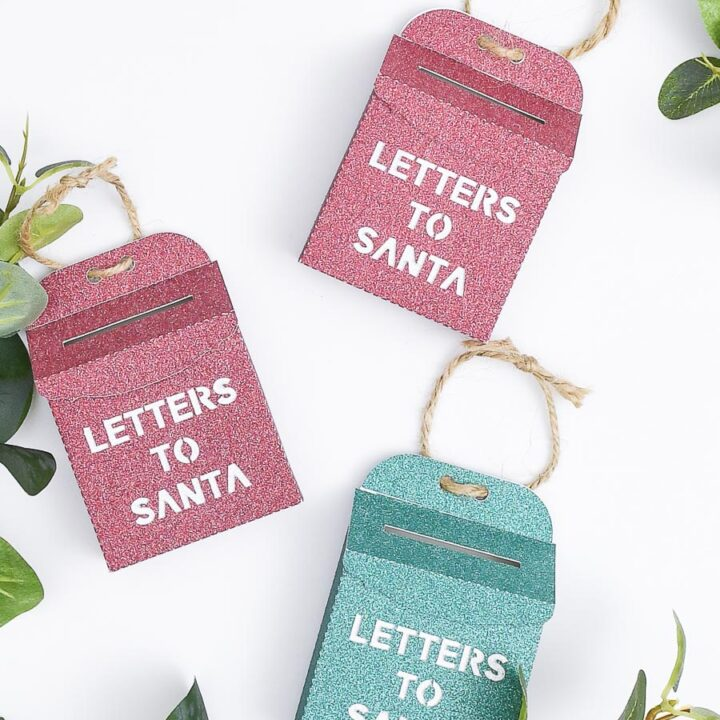 Three glittery Letters to Santa mailbox ornaments on a white background.