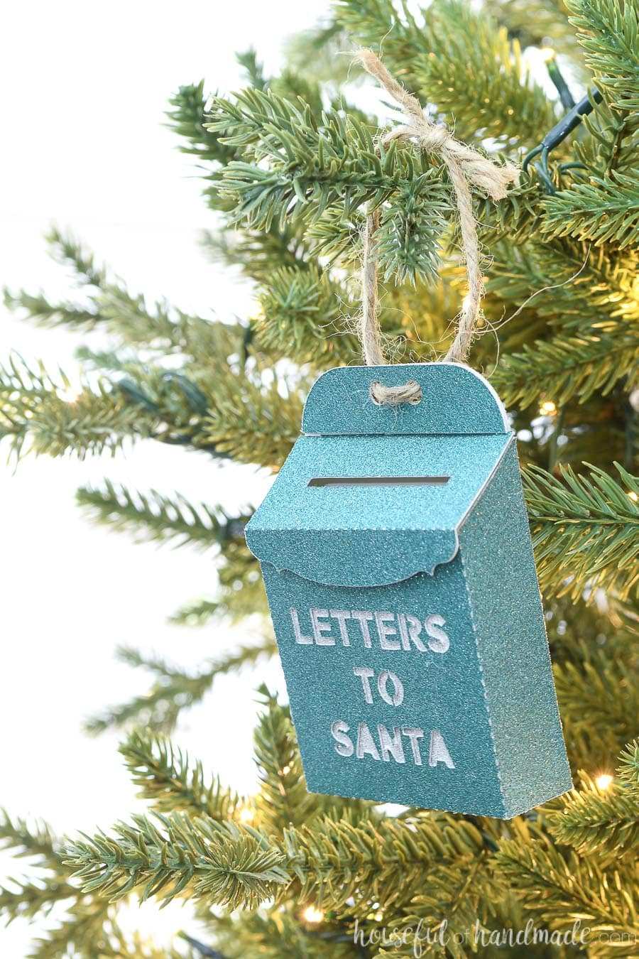Angled view of the turquoise santa mailbox Christmas ornament hanging on a tree.