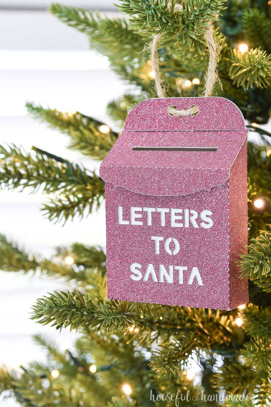 Red glitter paper ornament in the shape of a vintage letters to Santa mailbox hanging on a Christmas tree.
