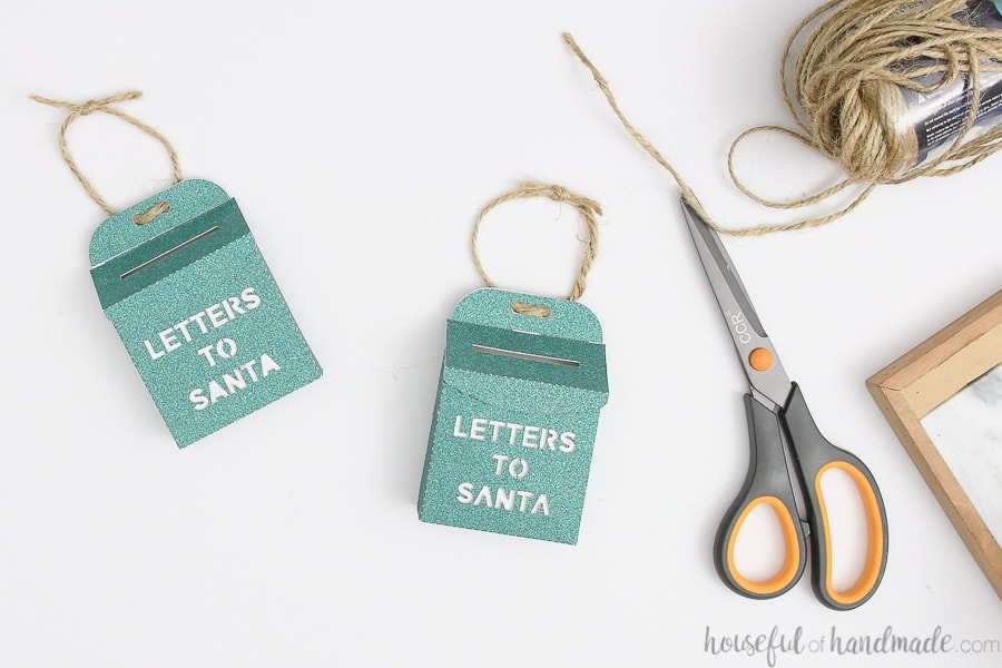Two green glitter Letters to Santa mailbox ornaments with twine tied to hang them on the tree.