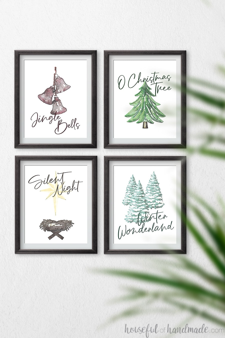 Four simple watercolor Christmas printables in black frames hanging on a wall.
