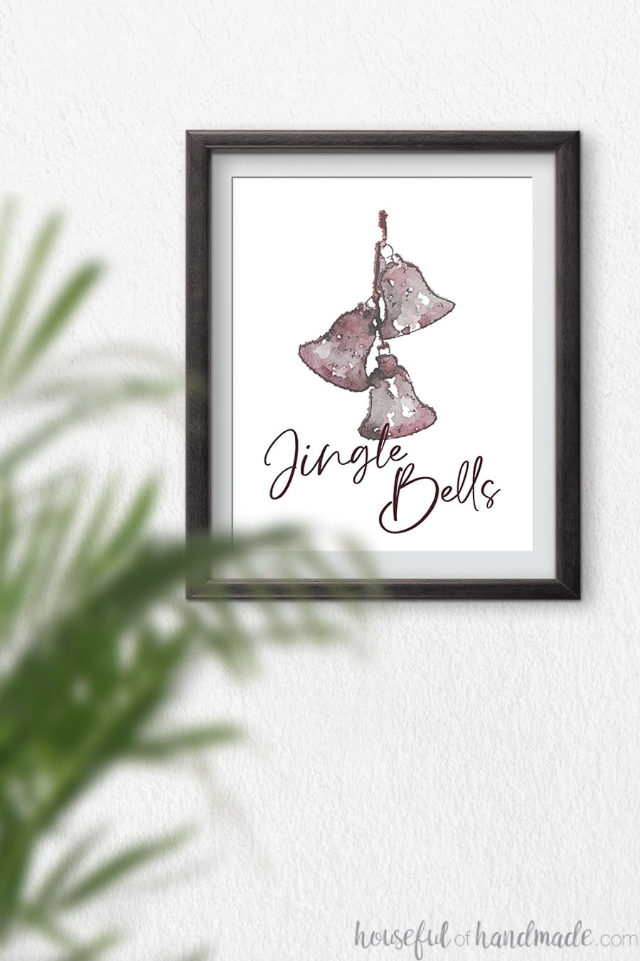 Watercolor of three reddish jingle bells hanging on a string with script writing Jingle Bells over the bottom of it.